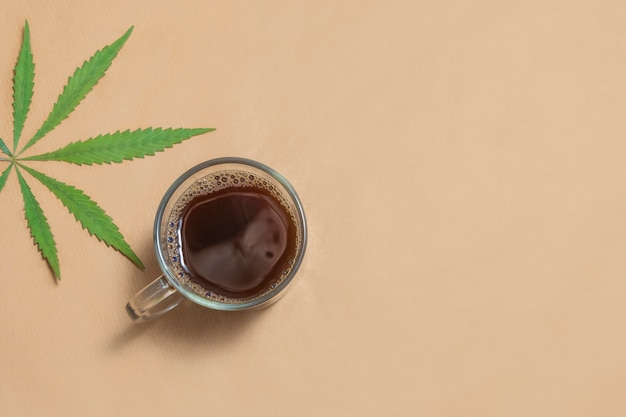 Zwarte koffie met cannabis, hennep, cbd of thc op een neutrale beige achtergrond