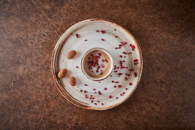 Zwarte koffie met gesublimeerde frambozen in een keramische lichte mok op bord in de buurt van snoepcacaobonen in
