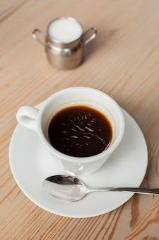 Zwarte koffie met melk op bureau bij koffiewinkel