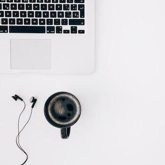 Zwarte koffiekop; oortelefoon en laptop op wit bureau