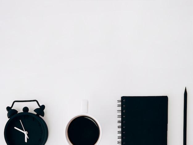 Zwarte koffiekop; wekker; dagboek en potlood op witte achtergrond met kopie ruimte voor tekst