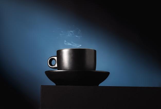 Zwarte koffiekopje op blauw