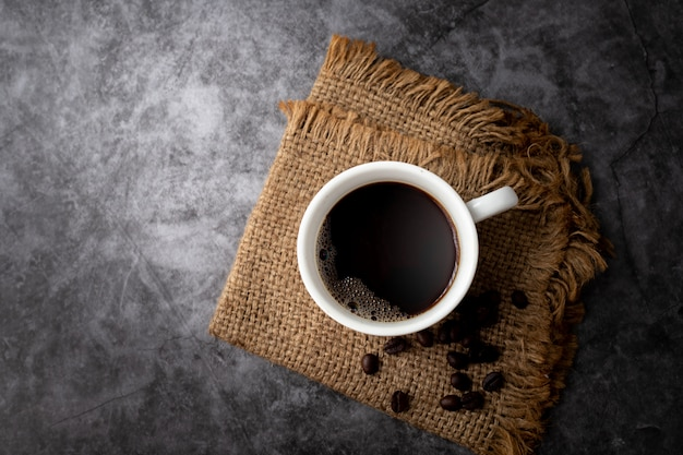 Zwarte koffiemok en koffiebonen op cement