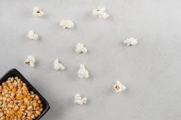 Zwarte kom gevuld met maïskorrels naast verspreide stukjes popcorn op marmeren tafel.