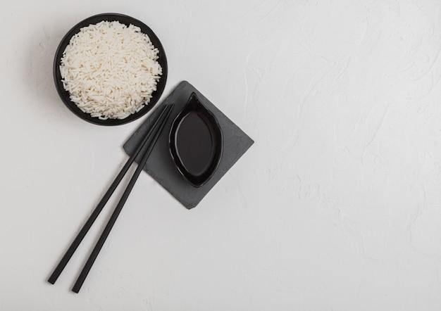 Zwarte kom met gekookte biologische basmati jasmijnrijst met zwarte stokjes
