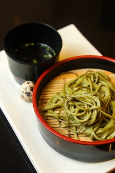 Zwarte kom met groene noedels met kwartelei en een saus geserveerd op een wit blad