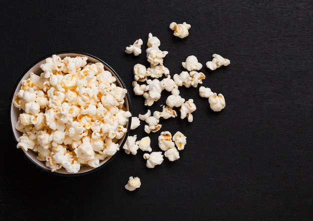 Zwarte kom met verse gezouten popcorn op houten achtergrond