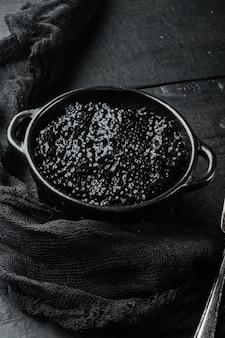 Zwarte kom met zwarte kaviaar, op zwarte houten tafel