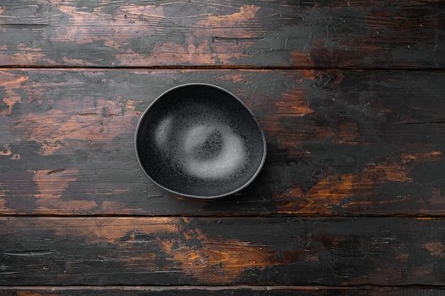 Zwarte kom set, met kopie ruimte voor tekst of eten, met kopie ruimte voor tekst of eten, bovenaanzicht plat lag, op oude donkere houten tafel achtergrond