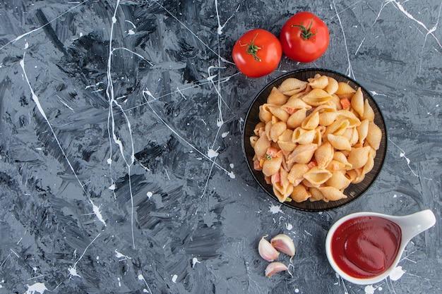 Zwarte kom smakelijke zeeschelppasta met ketchup op marmeren oppervlak. Gratis Foto