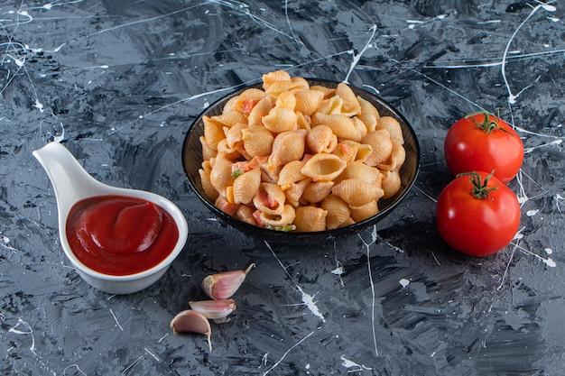 Zwarte kom smakelijke zeeschelppasta met ketchup op marmeren oppervlak.