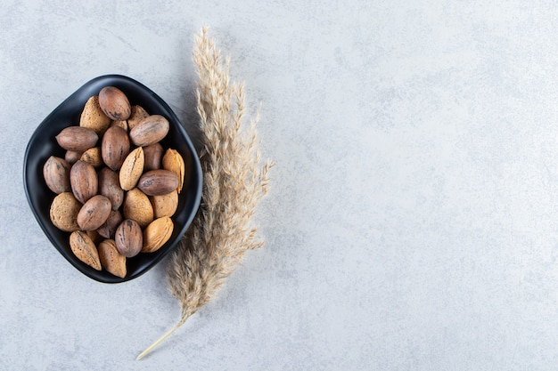 Zwarte kom vol gepelde amandelen en walnoten op steen.