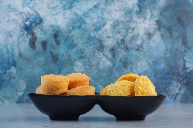 Zwarte kommen van mini zoete taarten en koekjes op blauwe achtergrond.