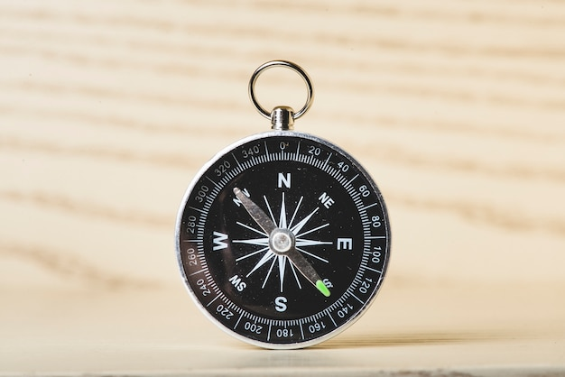 Zwarte kompas op houten oppervlak