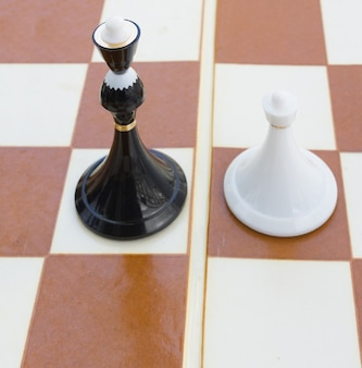 Zwarte koningin en witte pion op schaakbord