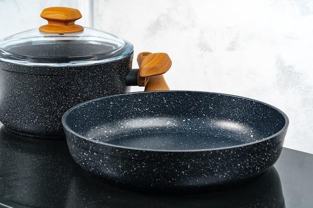 Zwarte kookgerei pan en pot op elektrisch fornuis close-up