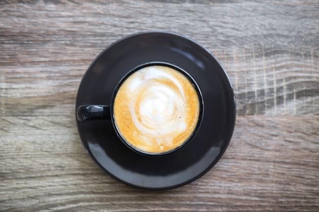 Zwarte kop koffie met melkschuim zo heerlijk op oude houten tafel