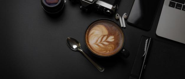 Zwarte kop koffie op donkere bureau met laptop, tablet, camera, benodigdheden en kopie ruimte