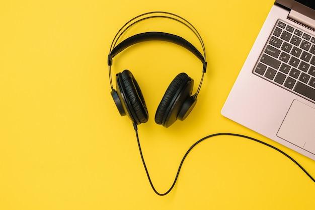 Zwarte koptelefoon aangesloten door een draad op de laptop op een gele achtergrond. het concept van werkplekorganisatie. apparatuur voor het opnemen, communiceren en luisteren naar muziek.