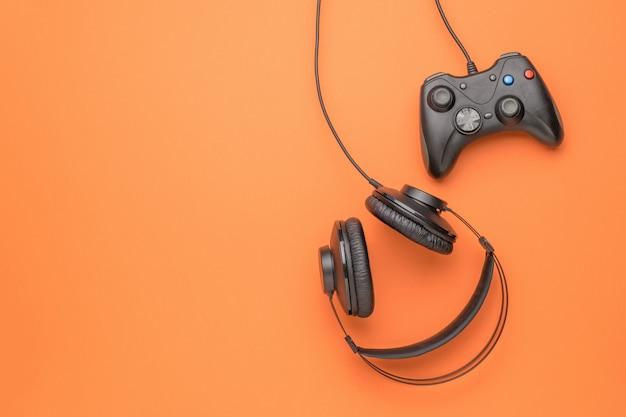 Zwarte koptelefoon en een zwarte gameconsole op een oranje achtergrond. plat leggen. plaats voor tekst.