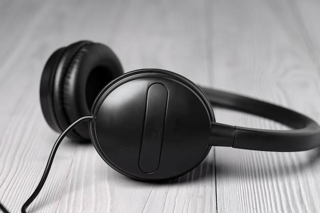 Zwarte koptelefoon met draad op houten achtergrond