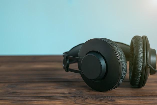 Zwarte koptelefoon op een houten tafel op een blauwe achtergrond. apparatuur om naar muziek te luisteren.