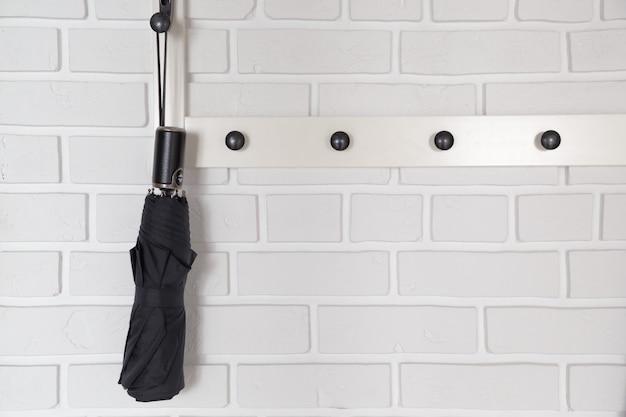Zwarte korte paraplu die op hanger in wit ganginterieur hangt.