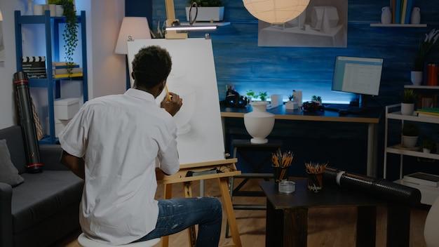 Zwarte kunstenaar die potlood op canvas gebruikt om vaas te tekenen