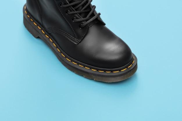 Zwarte laars op de blauwe achtergrond. mode schoenen stilleven. klassieke unisex zwarte veterlaars. close-up van boot met kopie ruimte voor tekst
