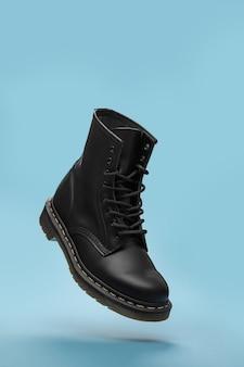 Zwarte laarzen in de lucht op de blauwe achtergrond. mode schoenen stilleven. klassieke unisex zwarte veterlaars. close-up van levitatie boot met kopie ruimte voor tekst