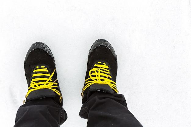Zwarte laarzen met gele veters op de sneeuw