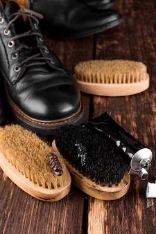 Zwarte laarzen met polijstapparatuur, borstel en polijstcrème