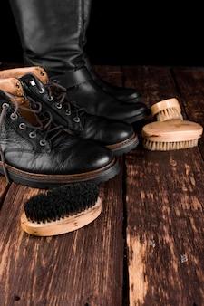Zwarte laarzen op hout met polijstapparatuur, borstel en polijstroom.
