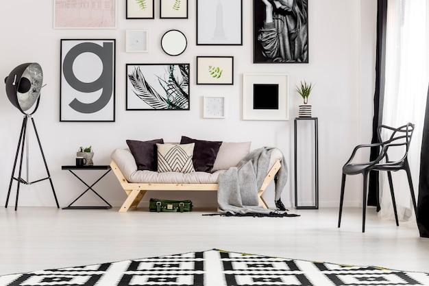 Zwarte lamp naast een bank in minimaal woonkamerinterieur met fauteuil en posters op witte muur