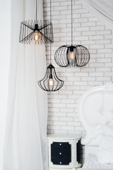 Zwarte lampen in licht slaapkamerbinnenland. drie moderne zwarte lampen hangen