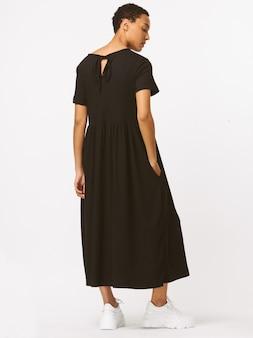 Zwarte lange vormloze jurk, lange mouwen, zwarte hoge schoenen. slank lichaam, zijdehuid. witte glimlach, lief gezicht, donkerbruin kapsel.