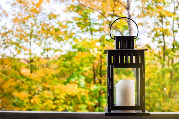 Zwarte lantaarn met een kaars op een terrasachtergrond van de herfsttuin