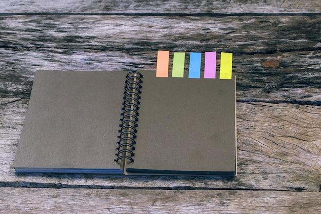 Zwarte laptop met kleuren notitie tabblad op houten tafel. case study concept