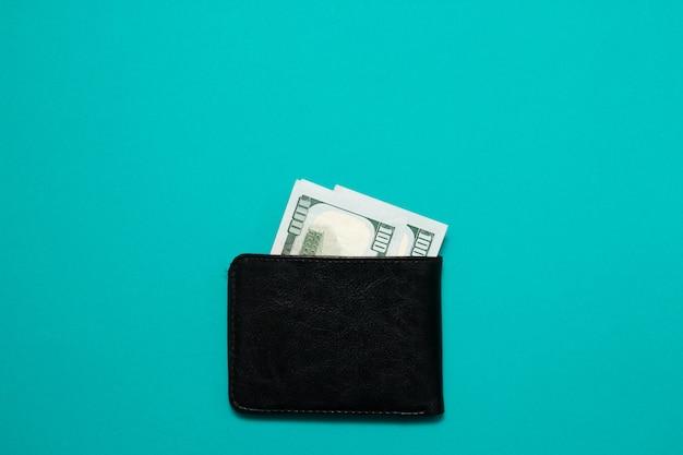 Zwarte lederen portefeuille met dollarbiljetten op blauwe achtergrond. heren portemonnee met geldwissels