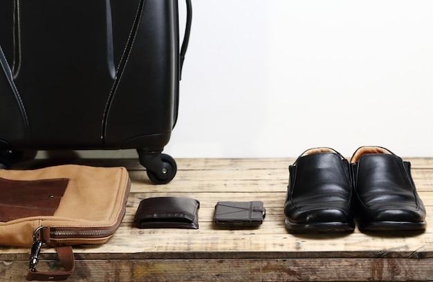 Zwarte lederen schoenen, portemonnee, mobiele smartphone en bagage reistas op de houten tafel