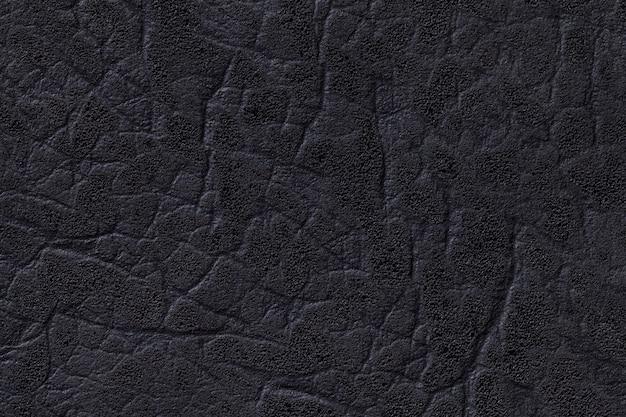Zwarte leerachtergrond met textuur, close-up.