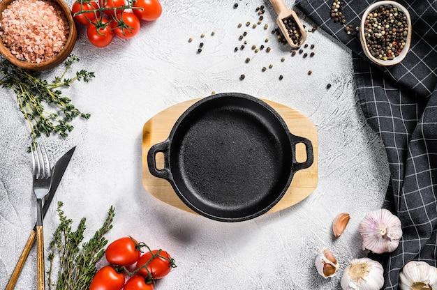 Zwarte lege pan in het centrum van verse rauwe groenten, groenten. gezond, schoon eten, veganistisch, dieetvoedselconcept. witte achtergrond