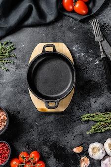 Zwarte lege pan in het centrum van verse rauwe groenten, groenten