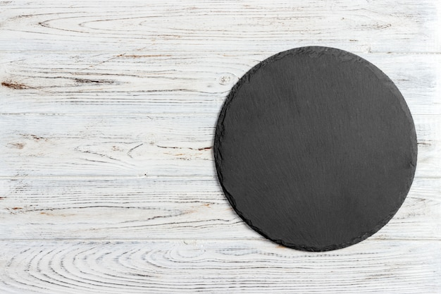 Zwarte lei om steen op houten achtergrond, hoogste mening, exemplaarruimte
