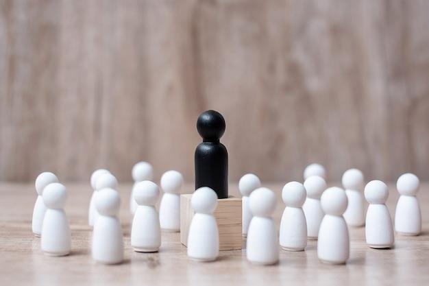 Zwarte leiderszakenman met menigte van houten werknemers. leiderschap