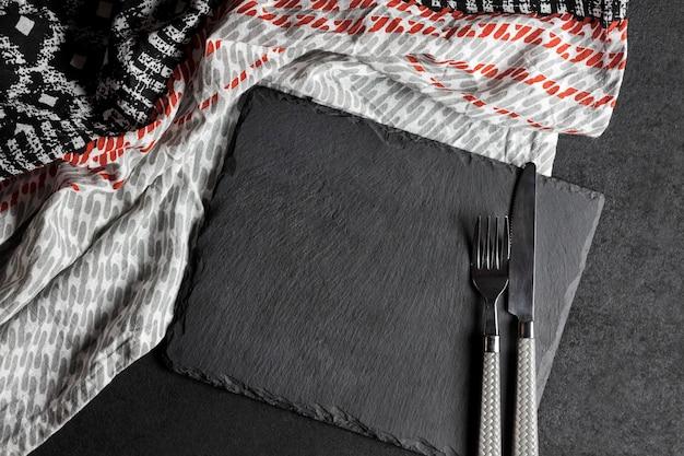 Zwarte leiplaat met vork en mes op zwarte achtergrond en tafelkleed. tafel opstelling.