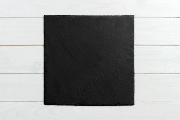 Zwarte leisteen op houten achtergrond. kopie ruimte