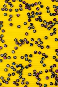 Zwarte letter kralen gele achtergrond