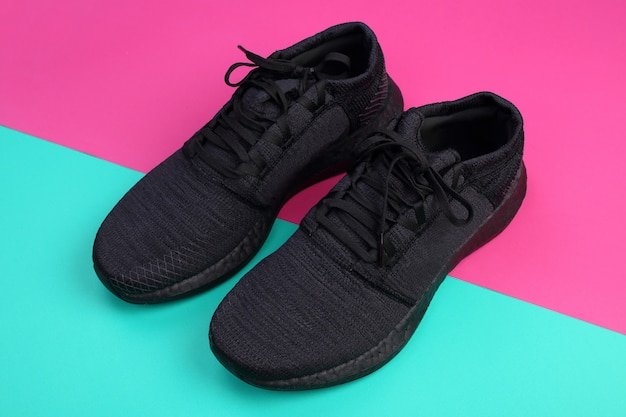 Zwarte loopschoenen op groen en roze pastel