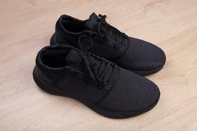 Zwarte loopschoenen op houten